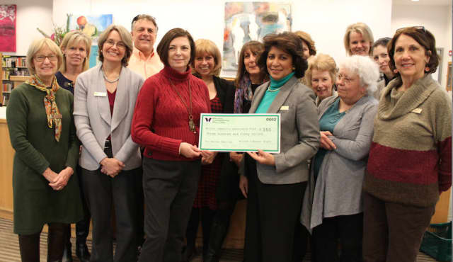 Cathy Pierce of Wilton Social Services accepts a donation check from Wilton Library executive director Elaine Tai-Lauria as members of the library staff look on.