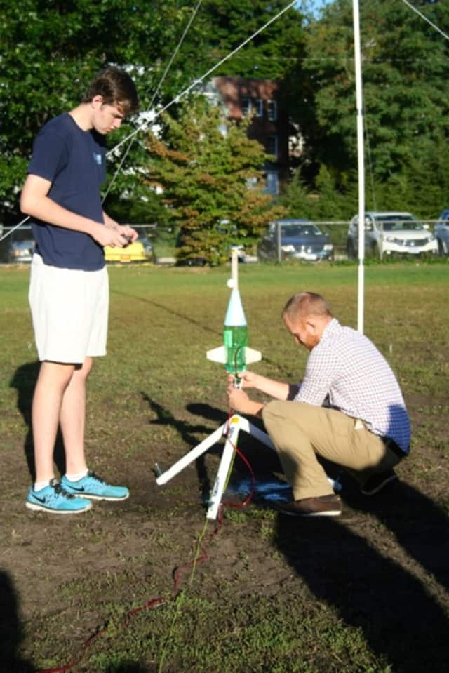 Advanced physics teacher Jonathan Peter and student Hank Thomas participating in a rocketry lab.