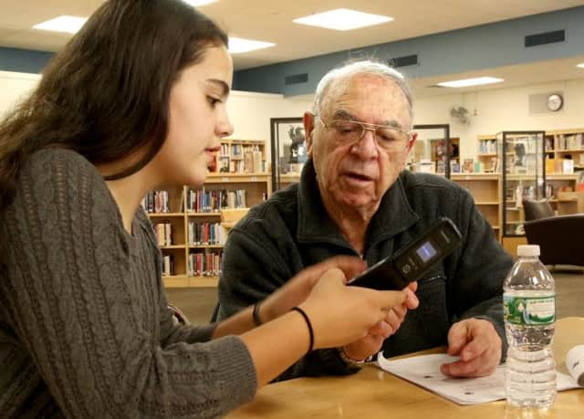 Tech Crew tutor Julia Remo instructs a senior citizen on how to take photo with a cell phone.