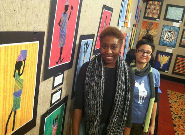 Kimberlyn McKoy, left, assistant curator for Picture That, and Liz Squillace, an assistant at Picture That, installing a show of student art work at the Palace Theatre.