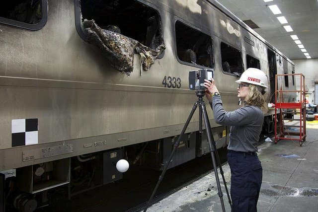 National Transportation Safety Board investigator Kristin Poland sets up 3D Laser Scanner to create model of the damaged rail car.