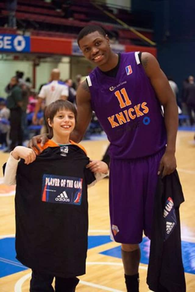 ADIDAS Player of the Game Cleanthony Early poses with ADIDAS Fan of the Game and birthday boy, Samuel Leviatin from Tarrytown.