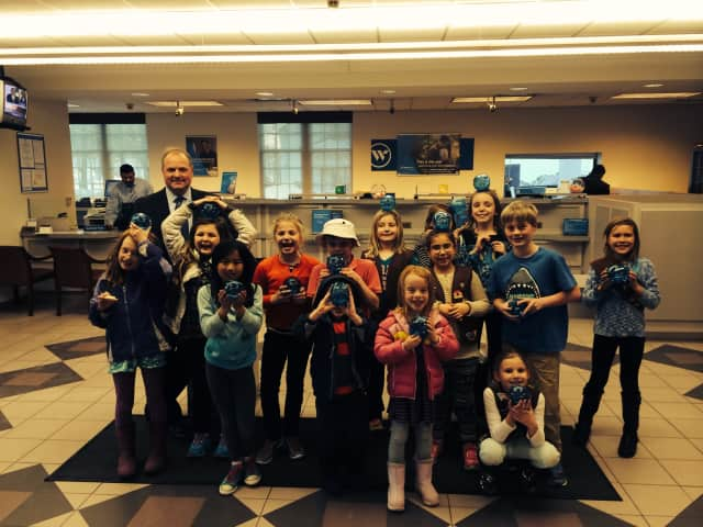 Third-graders from Ox Ridge Brownie Troop 50265 learn about saving their pennies from Webster Bank Vice President Peter Olson during a recent tour.