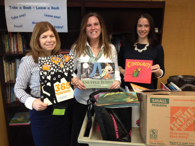 From left, Andrea Cohen, school social worker, Davenport Ridge Elementary School, Kerry Safir, president of JLSN, and Lindsay Bohnsack, president-elect of JLSN with new books for Davenport Ridge's lending library.