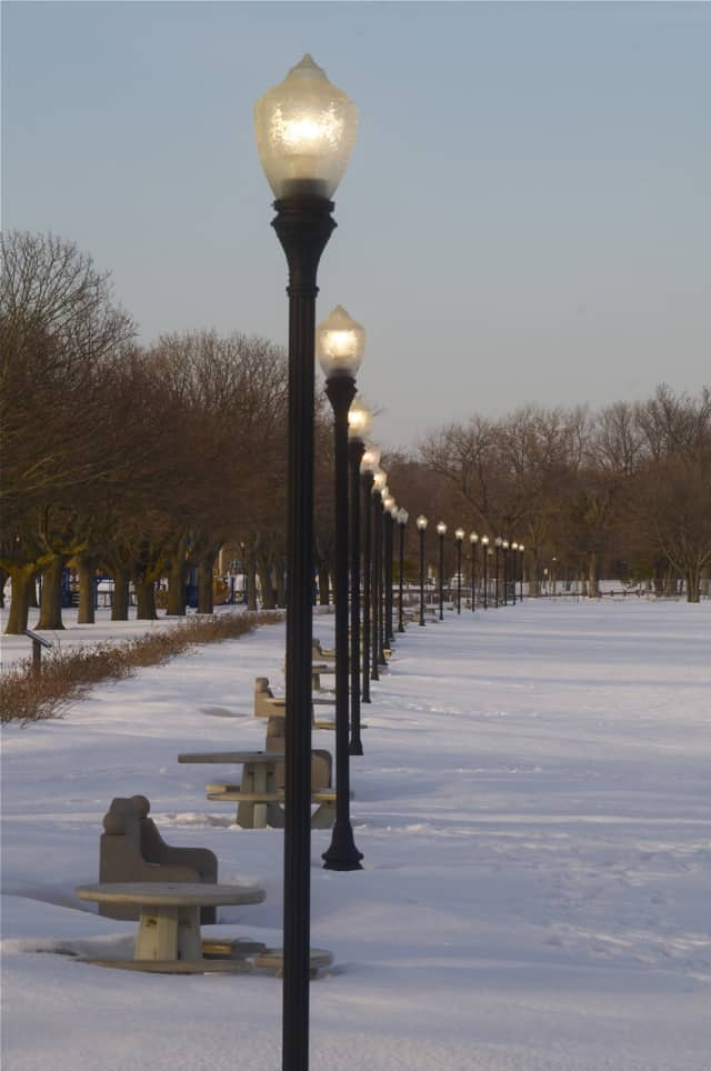 Lights come on adding to the beauty of the snow-covered beach.