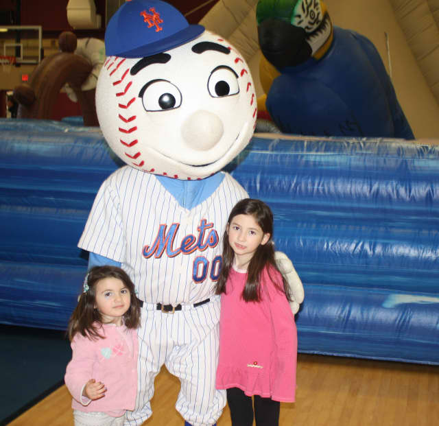 Two Lazzaro sisters, Aoife. left, and Maeve. right, of Carmel, pose with Mr. Met, who made a special appearance at the Children's Carnival for Charity at The Harvey School.