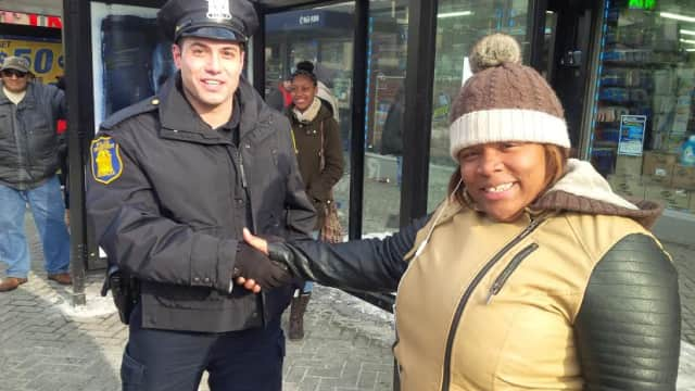 Yonkers Police Officer John Mucilli from the 4th Precinct shaking hands with a resident in Downtown Yonkers after the initiative was announced by Mayor Spano.