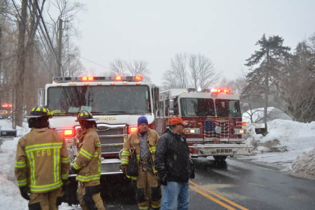 Firefighters near site of a home fire in Chappaqua. Firetrucks from Chappaqua and Millwood are pictured on Route 117.