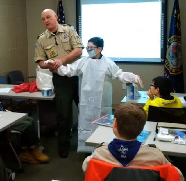 Scarsdale Sgt. Michael Siciliano suits up a Boy Scout in personal protective equipment during the first- aid workshop held at the Scarsdale Police Department.