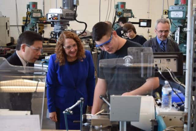 U.S. Rep. Elizabeth Esty and Deputy Labor Secretary Chris Lu look on as Abbott Tech sophomore Philip LoPiano works in the manufacturing lab at the Danbury technical high school.