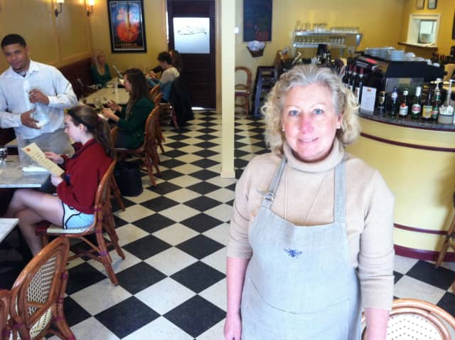 Café Ruche owner Barbara Chopin stands in her middle of her business as Brendon Ramsey helps with an order. The cafe opened in late December.