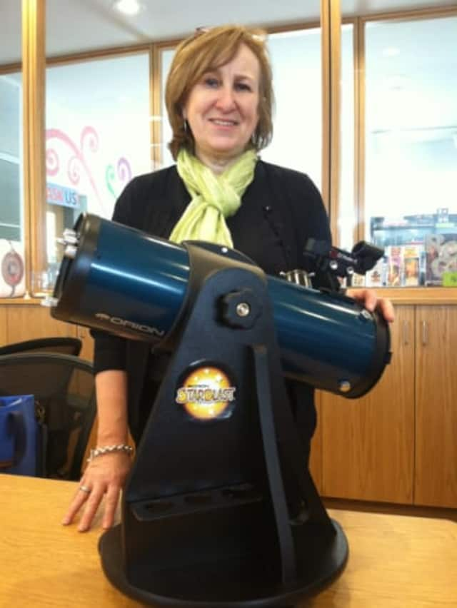 Susan Lauricella, head of Teen Services, Maker Space Coordinator at Wilton Library stands by the telescope that the library is now lending.
