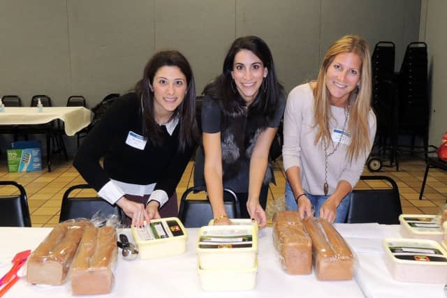 From left, event chairs Brooke Fina, Leslie Perelman, and Jodi Boockvar prepare sandwiches for donation.