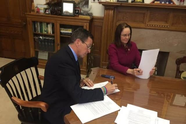 Connecticut Gov. Dannel Malloy signs the executive order Monday in his office.