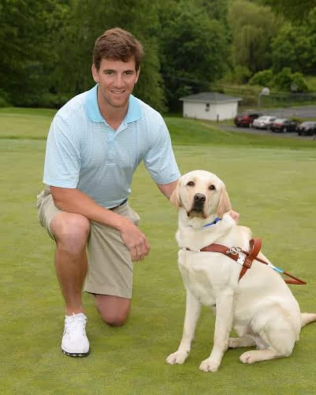 New York Giants Quarterback and nine-time Guiding Eyes for the Blind Golf Classic host Eli Manning with Guiding Eyes dog Jansen.