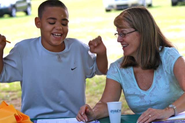 Cathy Osterhout, right, helps a student in a life skills class she teaches for Norwalk Grassroots Tennis.