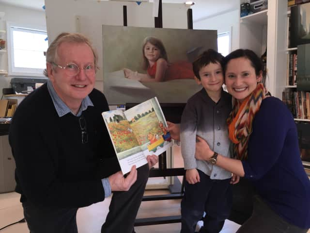 "A young reader and his mother visit with award-winning fine artist Ed Little in his art studio in Bridgewater and show him their favorite Imagination Library book, """"My Little Train"""" by Satomi Ichikawa."