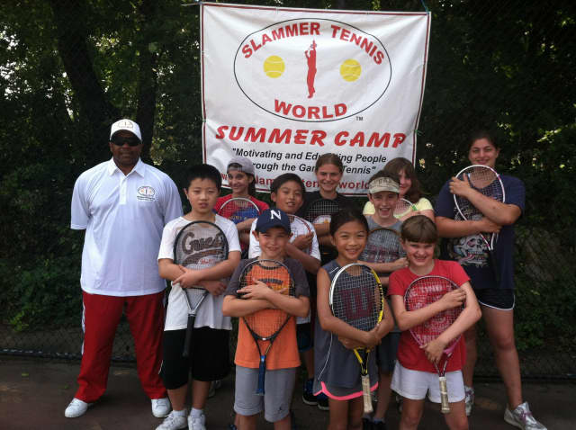 Marvin Tyler, back row, left, of Slammer Tennis World is registering children and adults for spring and summer programs in Norwalk.