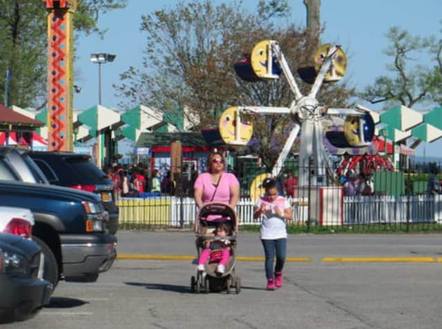 A mother and her two children leave Playland on opening weekend in May 2014.