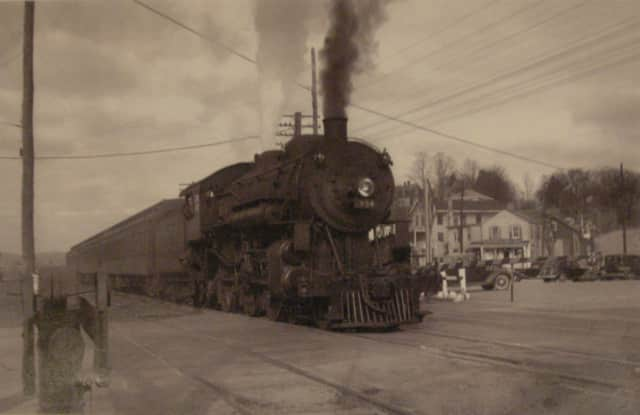 Depicted is a steam locomotive train passing through Bedford Hills in the early 1930s.