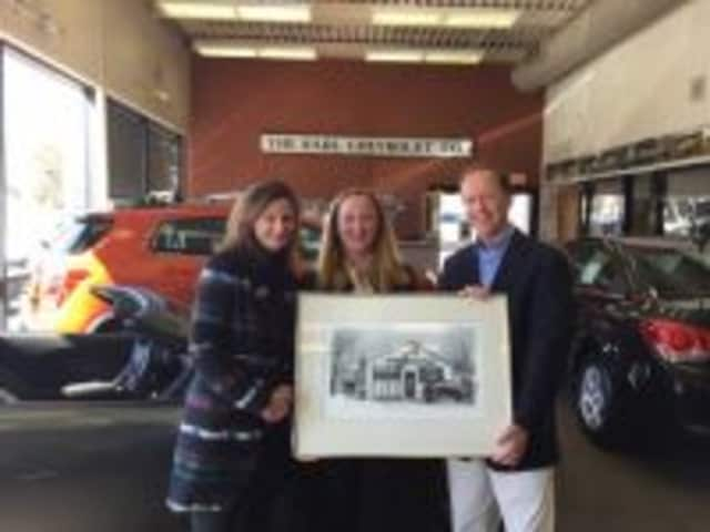 Photo Displaying a pen-and-ink drawing of the original KARL Chevrolet dealership on Railroad Avenue (now Elm St.) in New Canaan are (left to right) Arianne Kolb and Eleanor Flatow, co-directors of the Carriage Barn; Steve Karl, VP of  Karl Chevrolet.