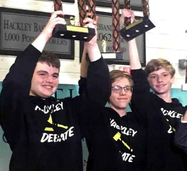 Hackley School's debaters team raise their trophies.