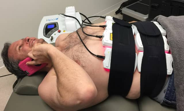 Eric Israel of Sandy Hook relaxes on the phone while he loses 3.5 inches at NY Health & Wellness during his fat-reduction treatment.