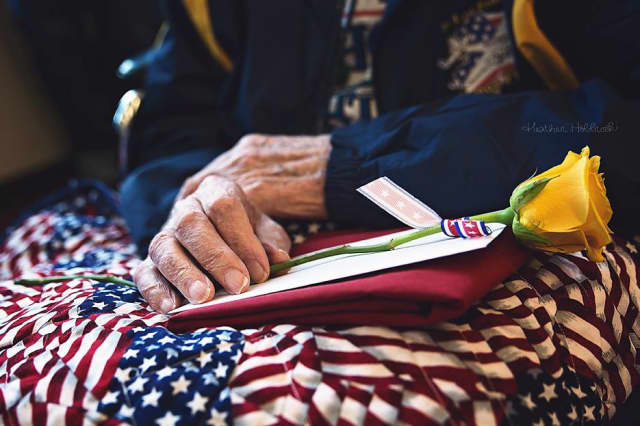A military veteran holds his quilt made by volunteers supporting Quilts of Valor.