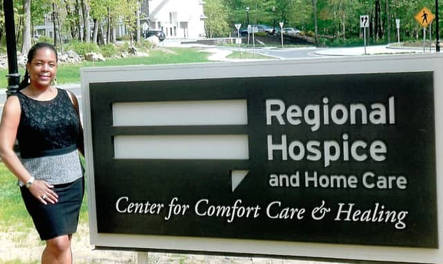 Valerie Cooper at the entrance sign to the Regional Hospice and Home Care Center for Comfort, Care and Healing in Norwalk.
