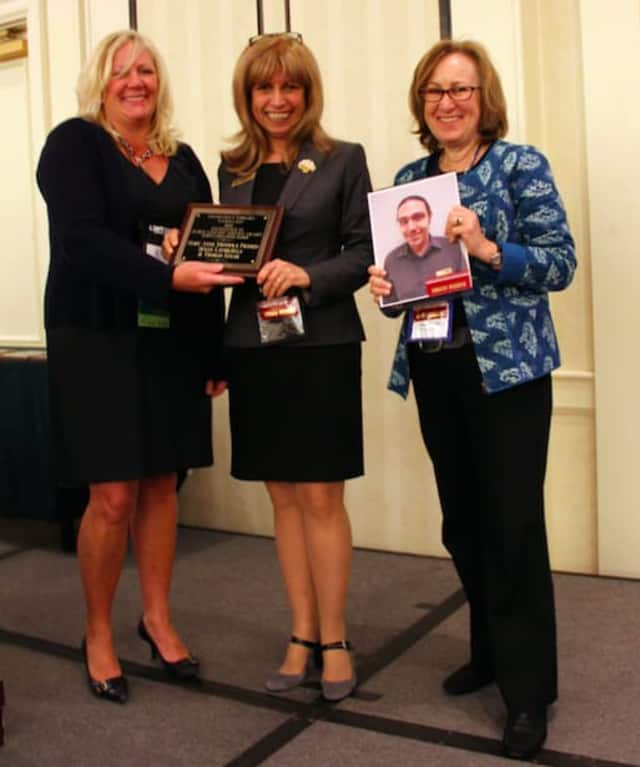 Dawn LaValle, director of library development at the Connecticut State Library, presents the Connecticut Library Association's 2015 Excellence in Public Library Service award to Wilton Library's Mary Anne Mendola Franco and Susan Lauricella.