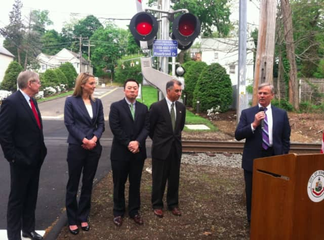 DOT Commissioner James Redeker speaks while from left: Mayor David Martin, state Reps. Caroline Simmons and William Tong and state Sen. Carlo Leone look on during an announcement heralding safety improvements at the Riverbend rail crossing.