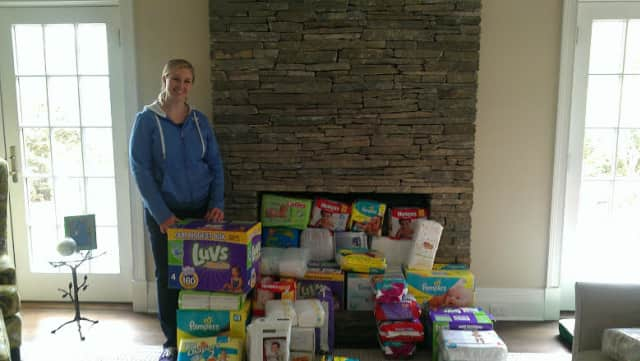 Junior League of Bronxvill chapter president Erica Sevilla with diapers and baby wipes collected in the drive.