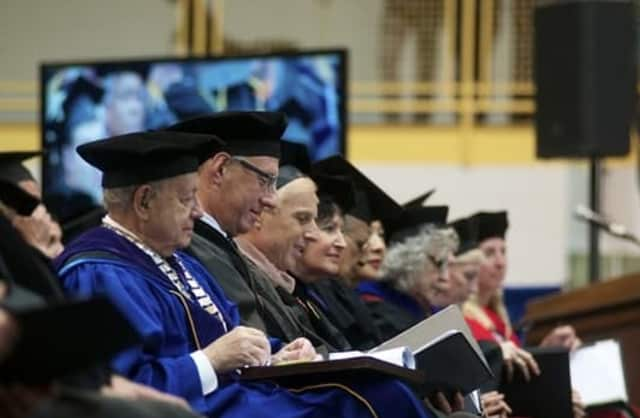 Pace University President Stephen Friedman, left, sits among University faculty at Tuesday's ceremony.