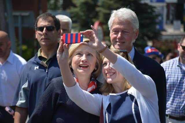 Bill and Hillary Clinton pause for what looks like a selfie attempt at the Chappaqua Memorial Day parade in May.