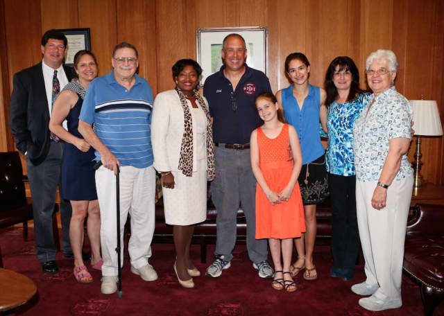 State Sen. Andrea Stewart-Cousins, fourth from left, and Chief Chris DePaoli, center, surrounded by his family in Albany on Thursday.