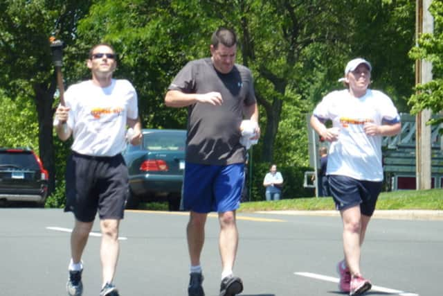 "Westport Police Officer David Wolfe, left, runs with the Special Olympics ""Flame of Hope"" torch in a previous year."
