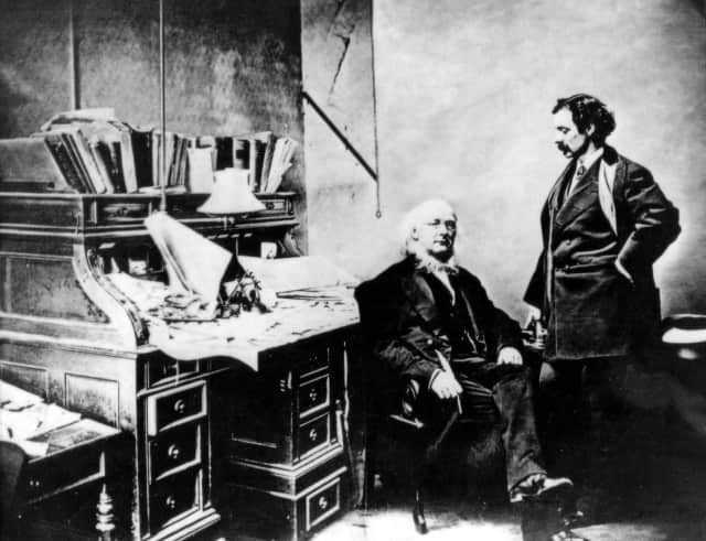Horace Greeley seated at his desk in the New-York Tribune with publisher Whitelaw Reid.
