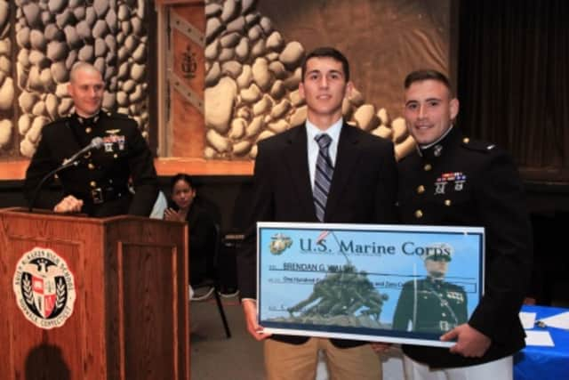 Maj. Thomas Abbott, left, and 1st Lt. Stefan Milan, right, present Brendan Walsh with a $180,000 scholarship during a high school awards ceremony June 3 at the Brien McMahon High School.