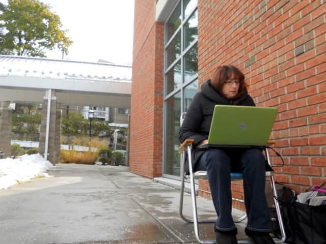 A resident sits outside the Ossining Public Library in October 2011 after a freak snowstorm knocked out power to much of Westchester County.