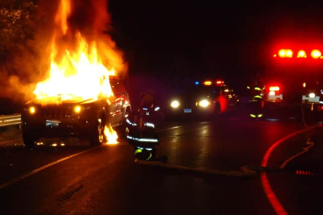 Norwalk firefighters extinguish a burning car on the Exit 15 northbound ramp to the Route 7 Connector Wednesday night.