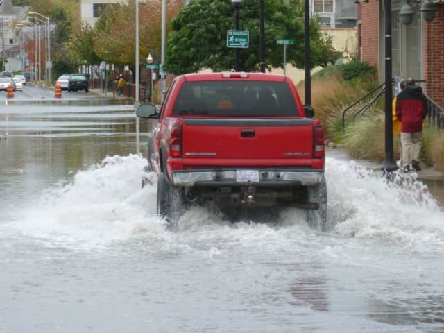 A truck bypassed barriers blocking off a section of Water Street in Norwalk as tidal surges flooded the street during a previous storm.