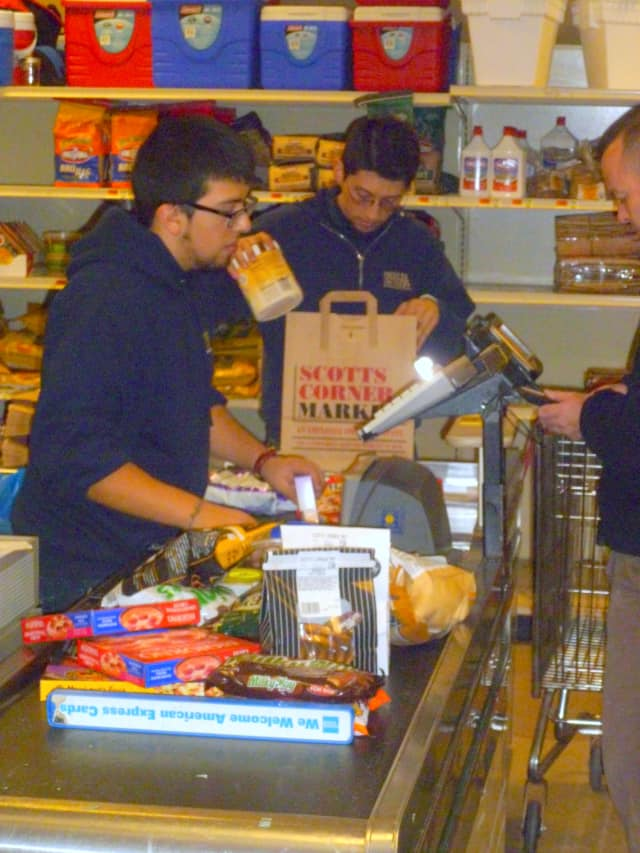 Scotts Corner Market staff check out customers Monday morning. They've been very busy since Saturday morning.