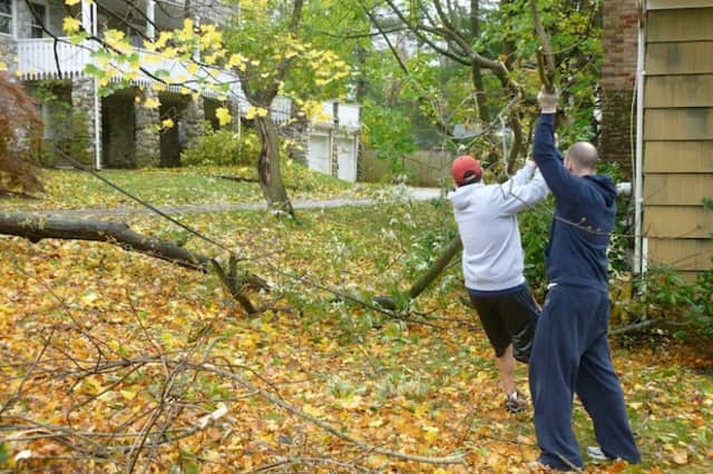 John Soler and Adam Nadborny, residents of Greenacres Avenue in Hartsdale, move a tree that fell down in their neighbor's yard.