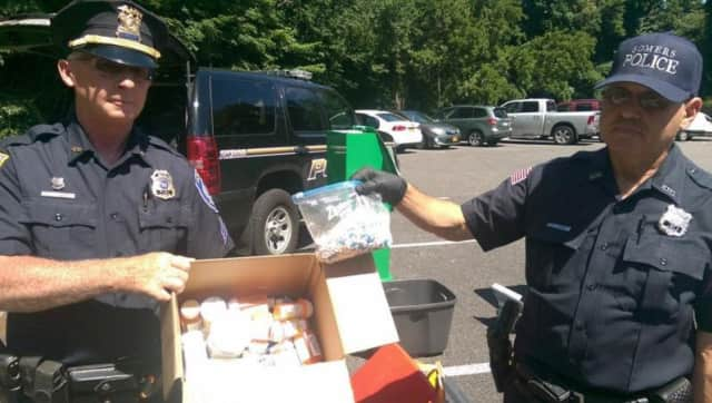 Somers Police Chief Michael Driscoll, left, and an unidentified police officer, display some of the medications collected in June at the Somers Town House.
