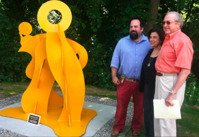 "Carole Eisner, center, a sculptor and artist, with Wilton First Selectman Bill Brennan, at right, and Jeff Meuller, gallery director at Silver Mines Arts Center, at the unveiling of Eisner's welded metal sculpture, ""Konnected."""