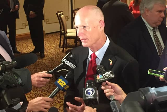 Florida Gov. Rick Scott talks to reporters after addressing a roundtable group of business leaders at the Norwalk Inn Friday.