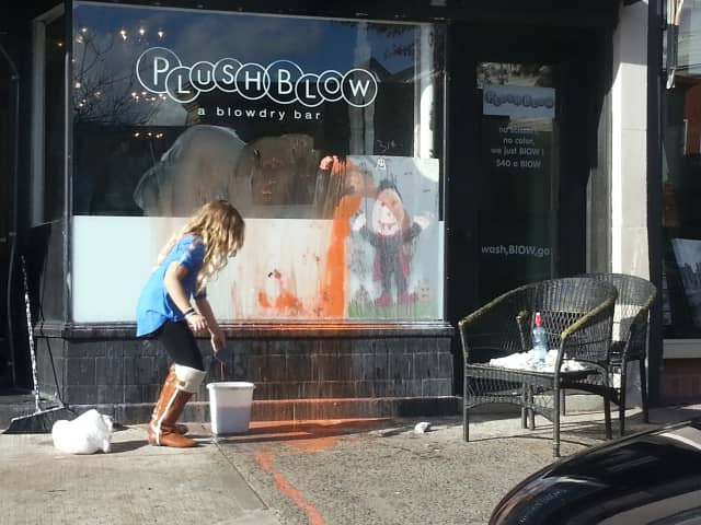 A young Rye resident washes down Halloween window paintings on Wednesday in front of PushBlow on Purchase Street.