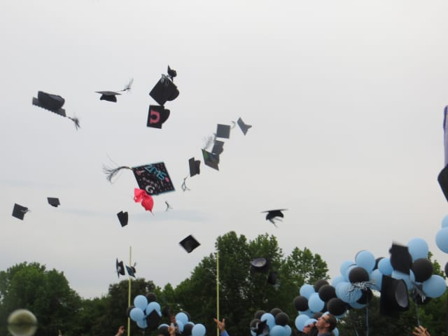 Rye Neck High School graduates toss their caps after a commencement ceremony in Mamaroneck. The district was among the top Westchester schools having the best teachers, according to a new survey.
