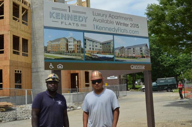 Construction workers pose by the 1 Kennedy Flats apartment development in downtown Danbury.
