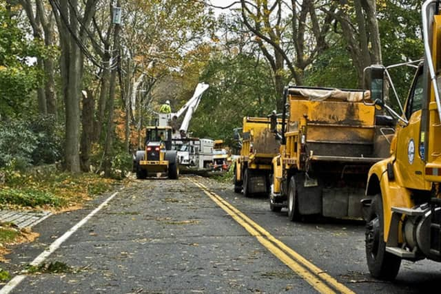 Connecticut Light & Power workers clear a road in Darien following Hurricane Sandy.